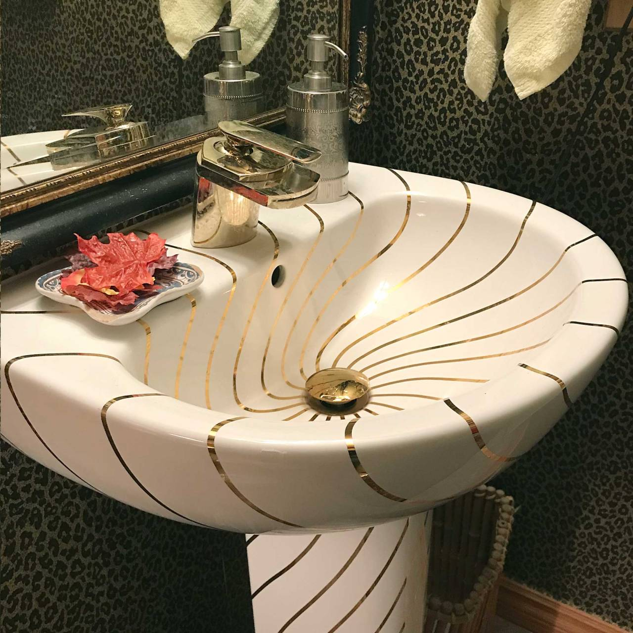 gold lines painted on pedestal sink